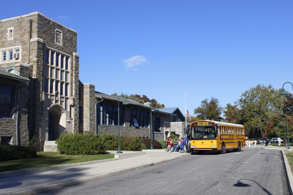 Merion Elementary School.  Traditional-looking school, blue skies and kids getting on the yellow school bus: this looks like a quintessential scene played out through suburban America
